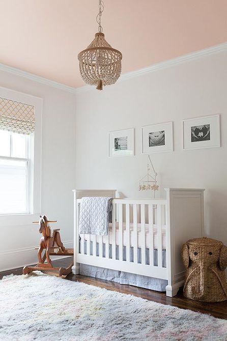 Habitación infantil simple con tonos neutros y techo rosa pintado