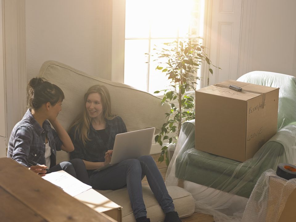 Two women moving into new home working on a laptop