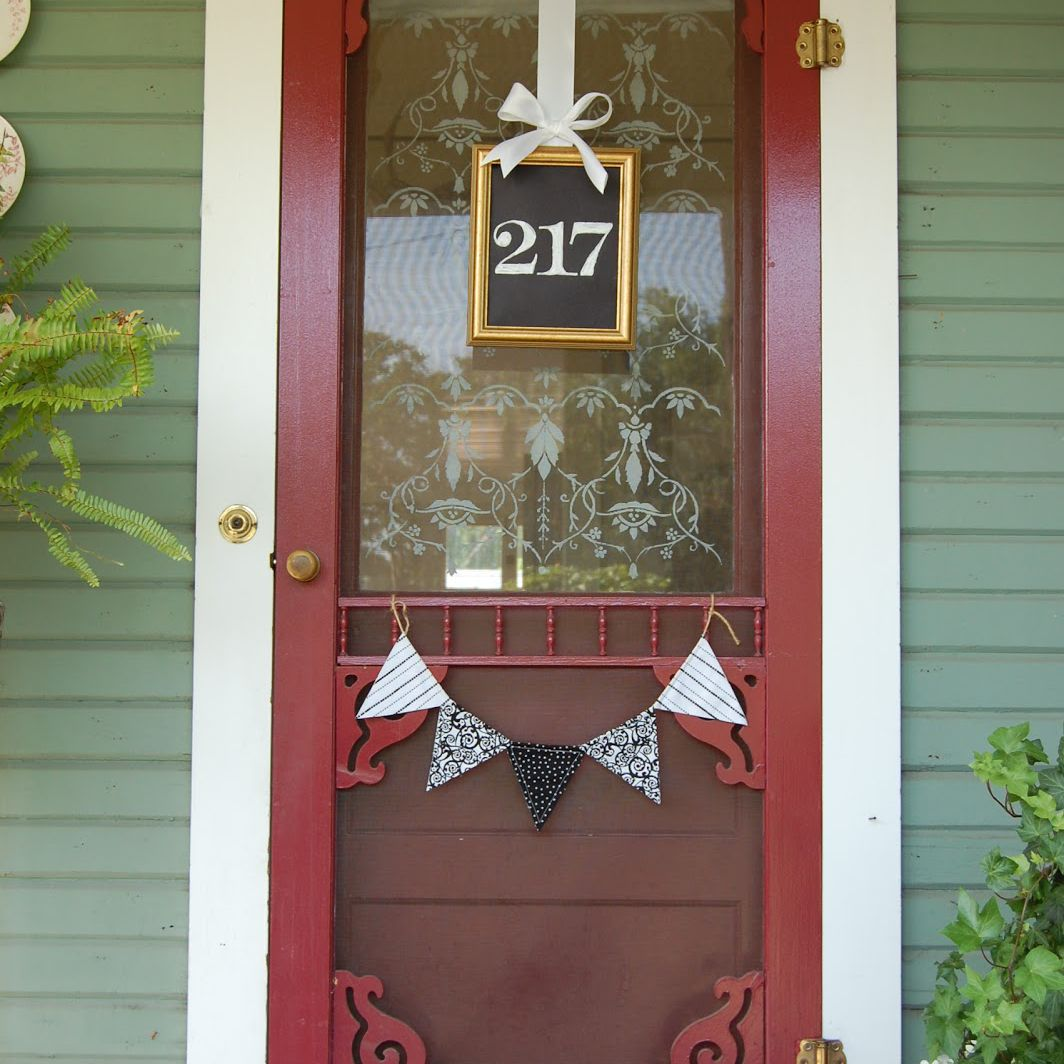 A red door with a hanging number sign in front.