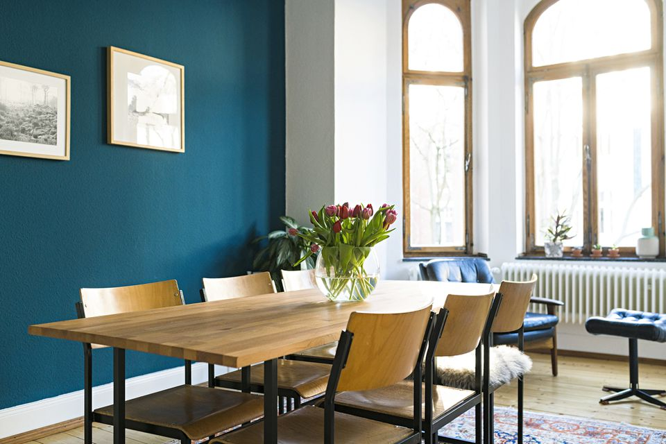 Dining room with dark blue accent wall and large window bay.