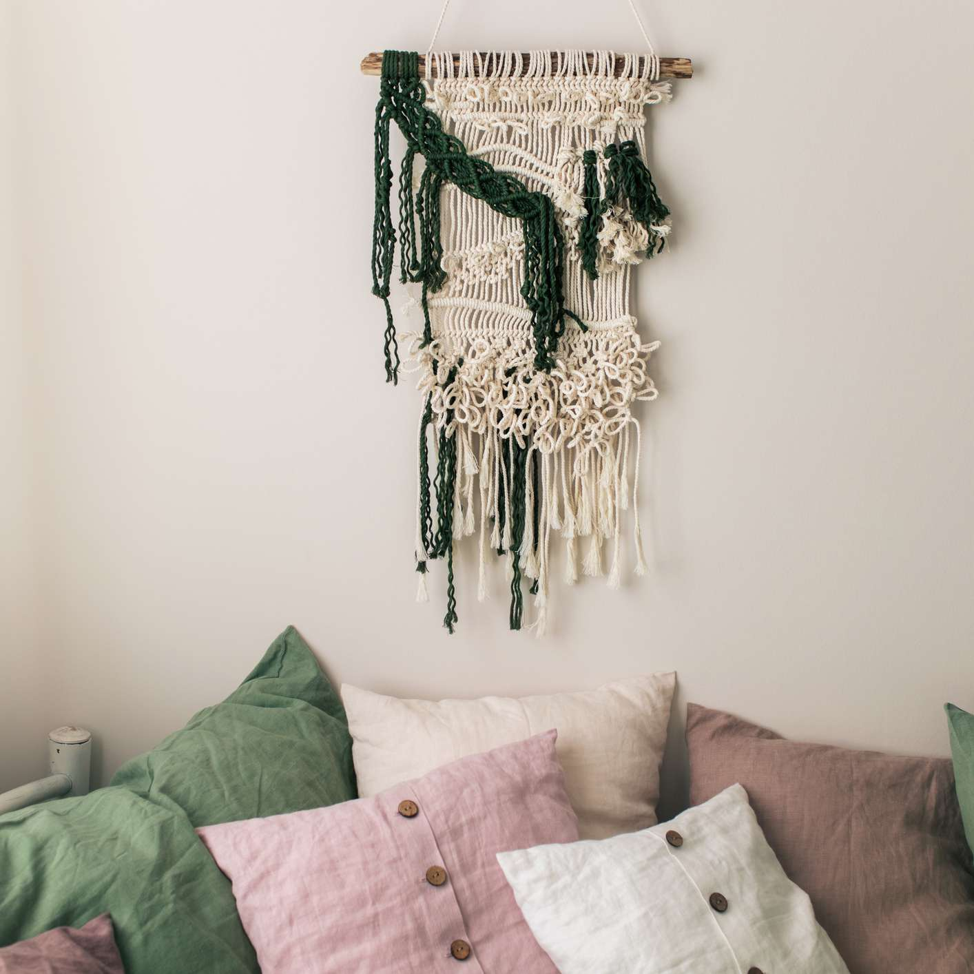 A bedroom with blush pink and macrame accents