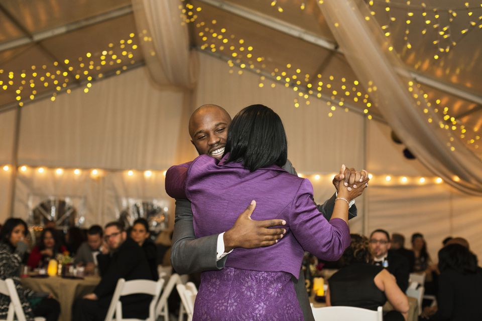 Black groom dancing with mother at reception