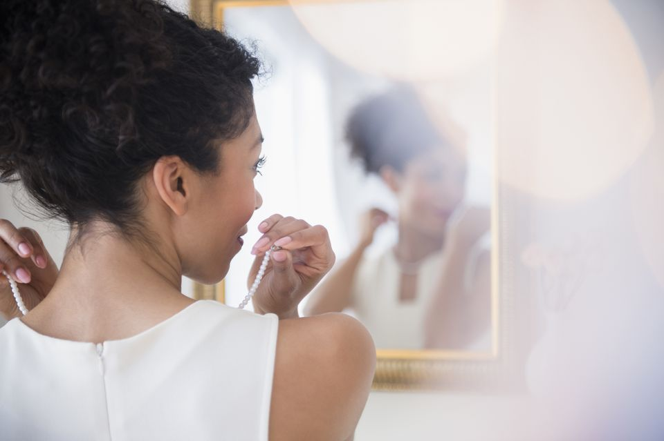 Mixed race woman fastening pearl necklace in mirror