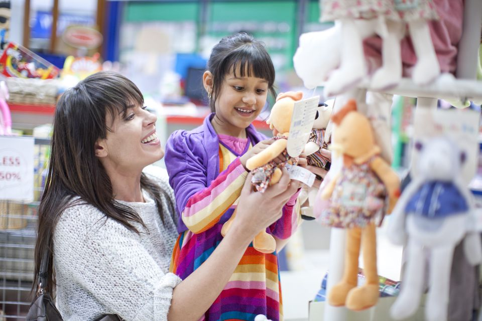 Mother and child shopping for toys at a store.