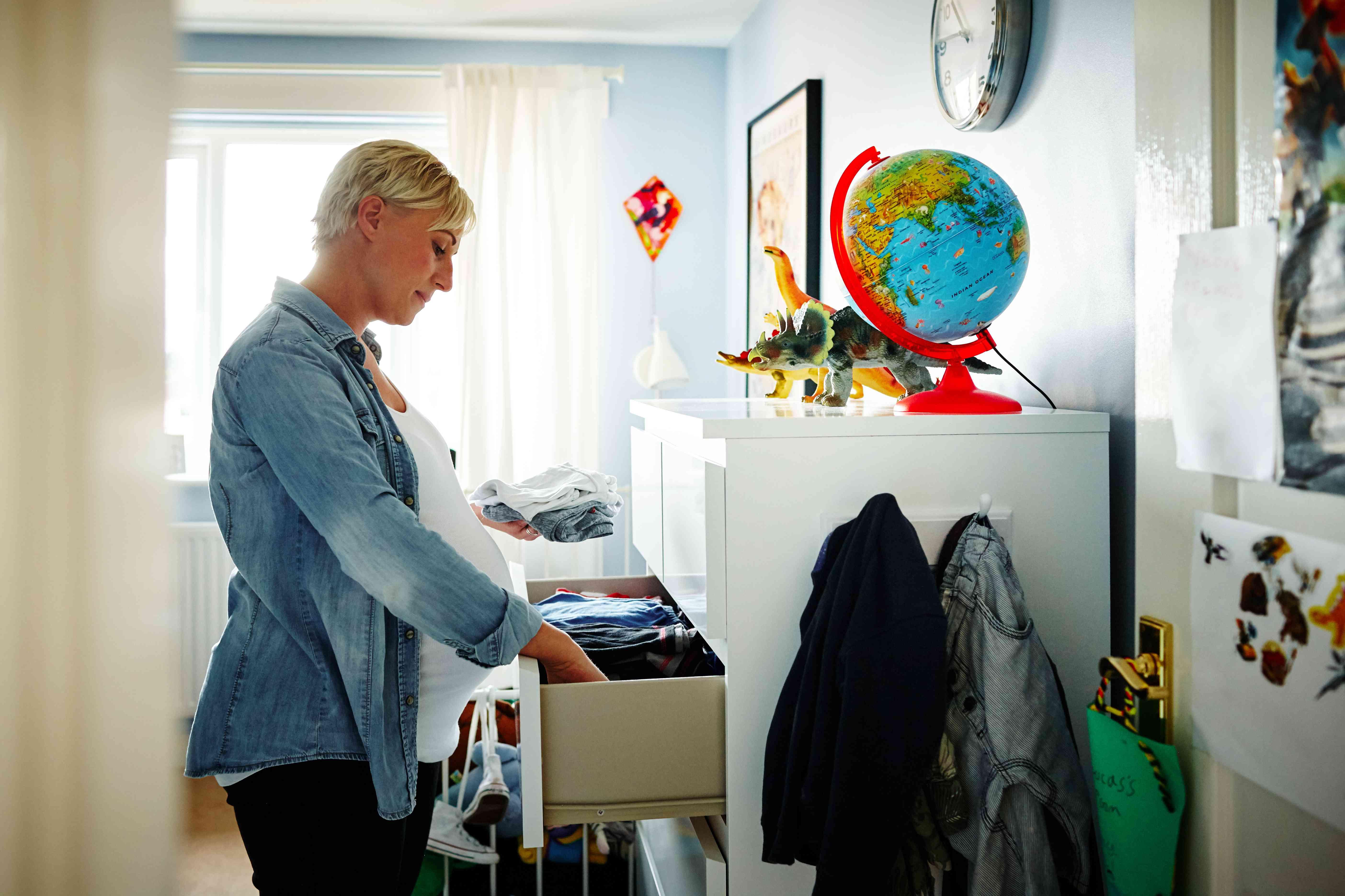 Pregnant woman arranging the wardrobe