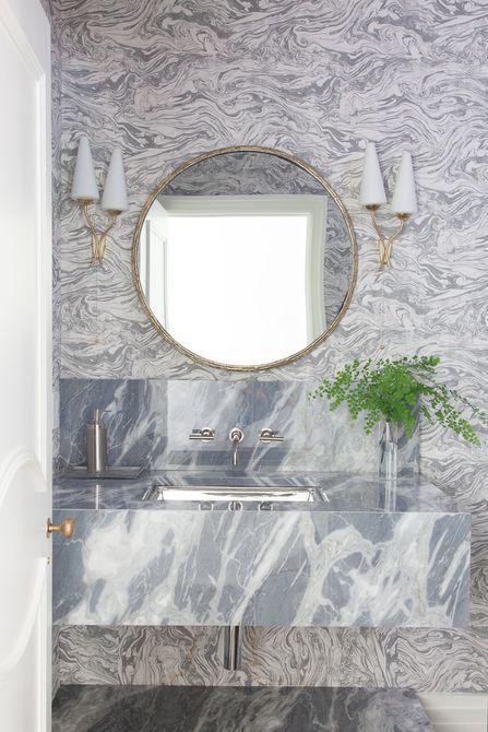 Lavabo y placa para salpicaduras de mármol en el baño con papel tapiz de remolino de mármol
