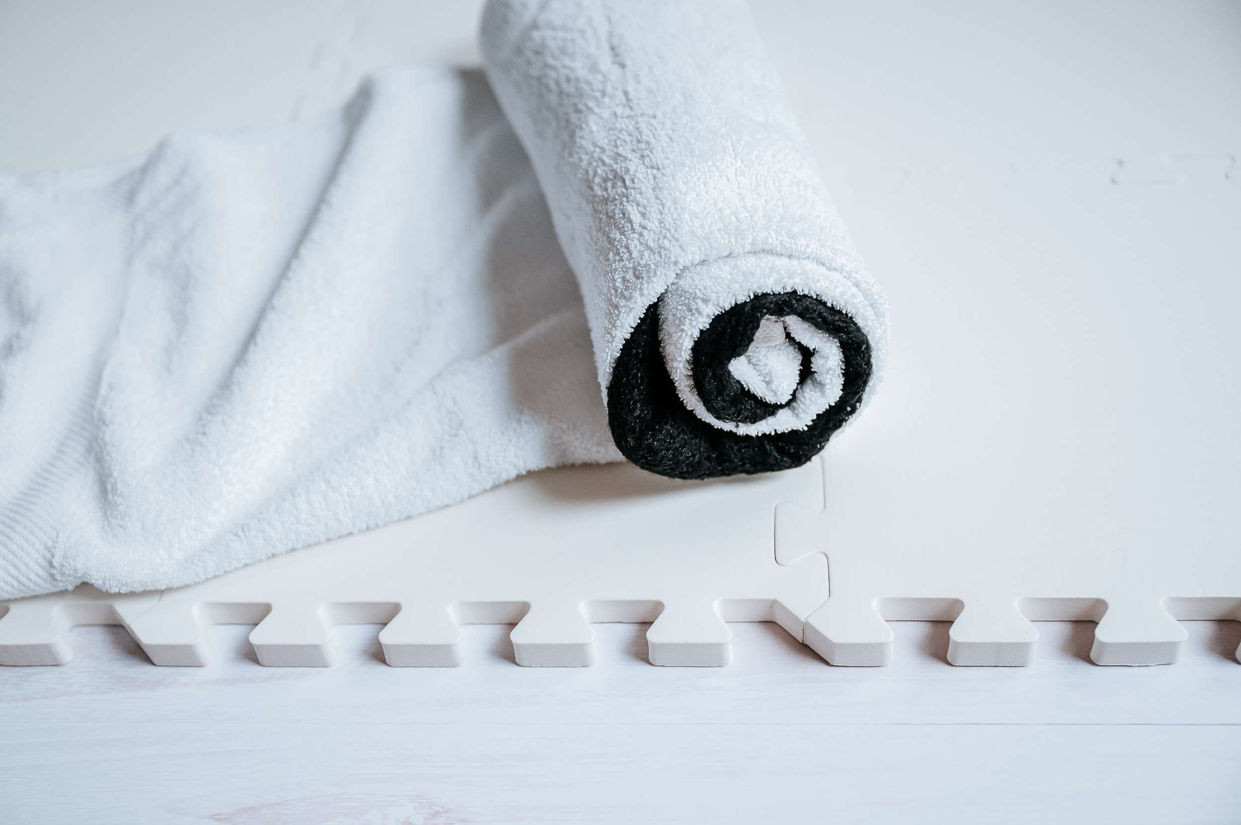 A sweater rolled up in a thick cotton towel on a board