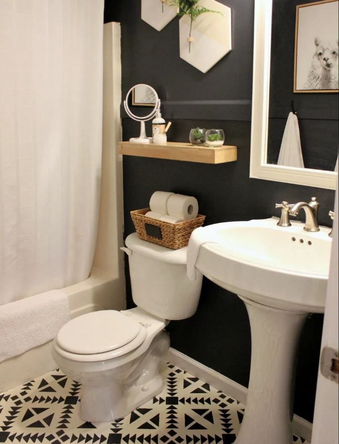 Updated small bathroom with black painted walls and geometric tiled floors.