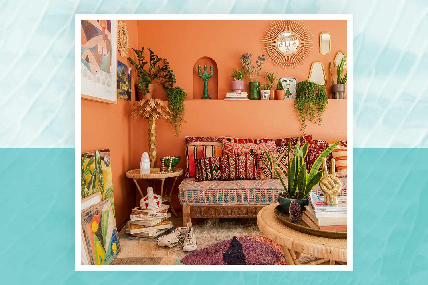 Justina Blakeney living room warm terra cotta walls, plants, and colorful rug, pillows, and wall art for Jungalow