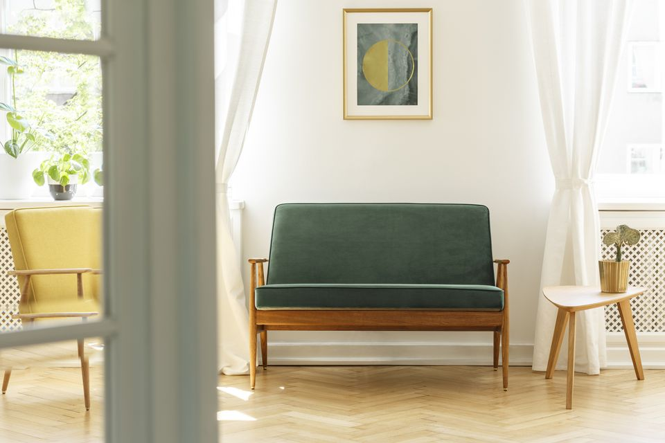 Poster above green wooden sofa in vintage living room interior with white table