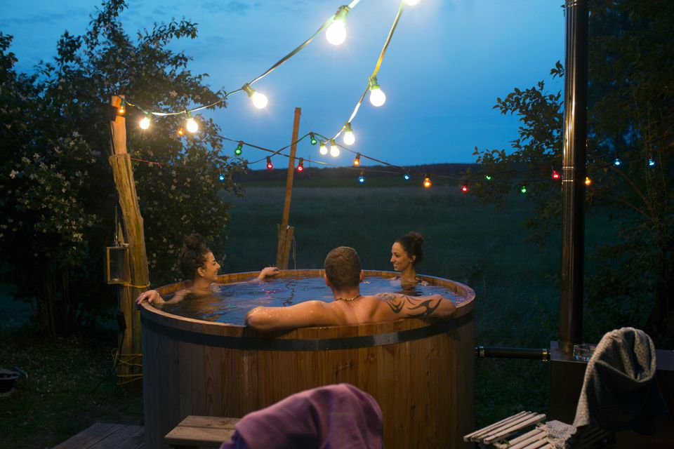 Three friends in circular hot tub outside at nighttime with stringed lights above them.