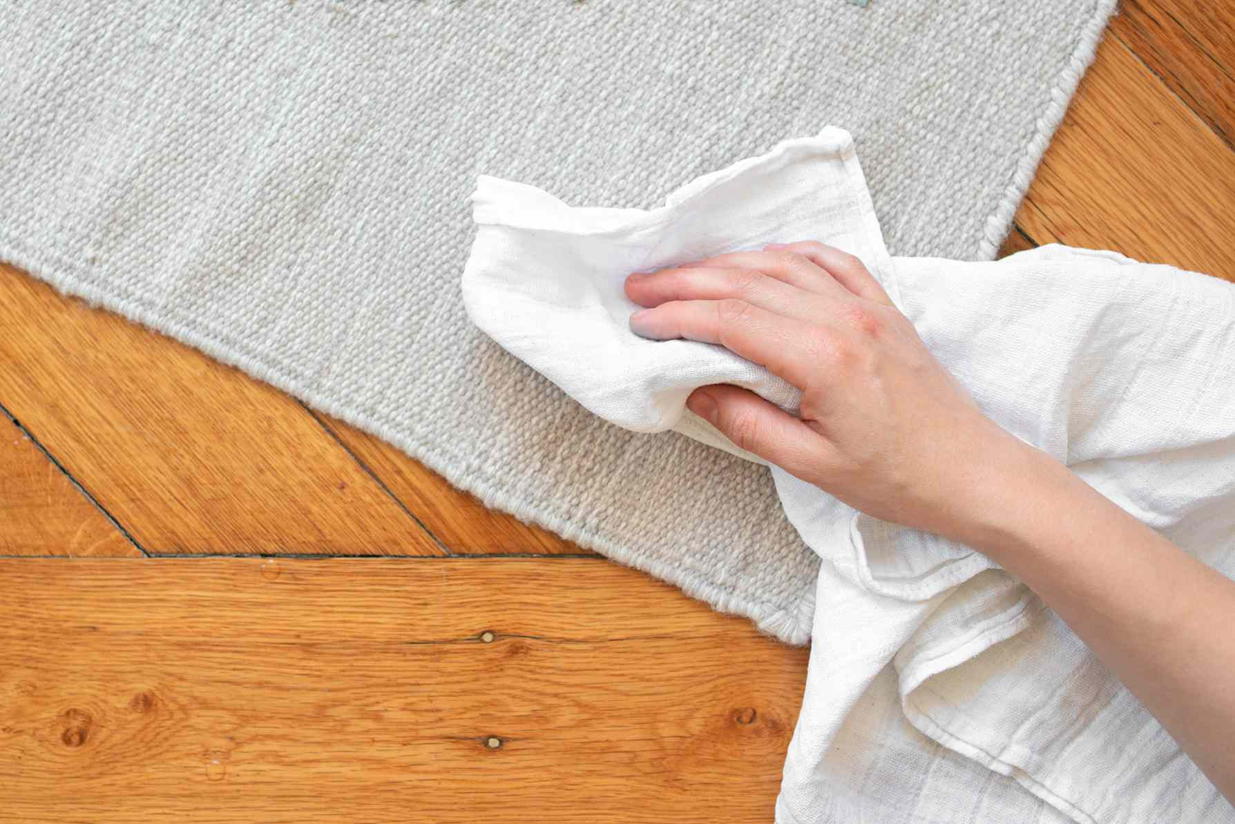 person blotting a rug with a clean cloth