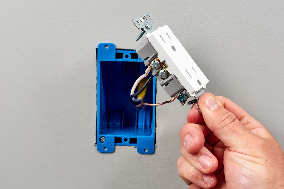 Outlet receptacle being installed inside blue box