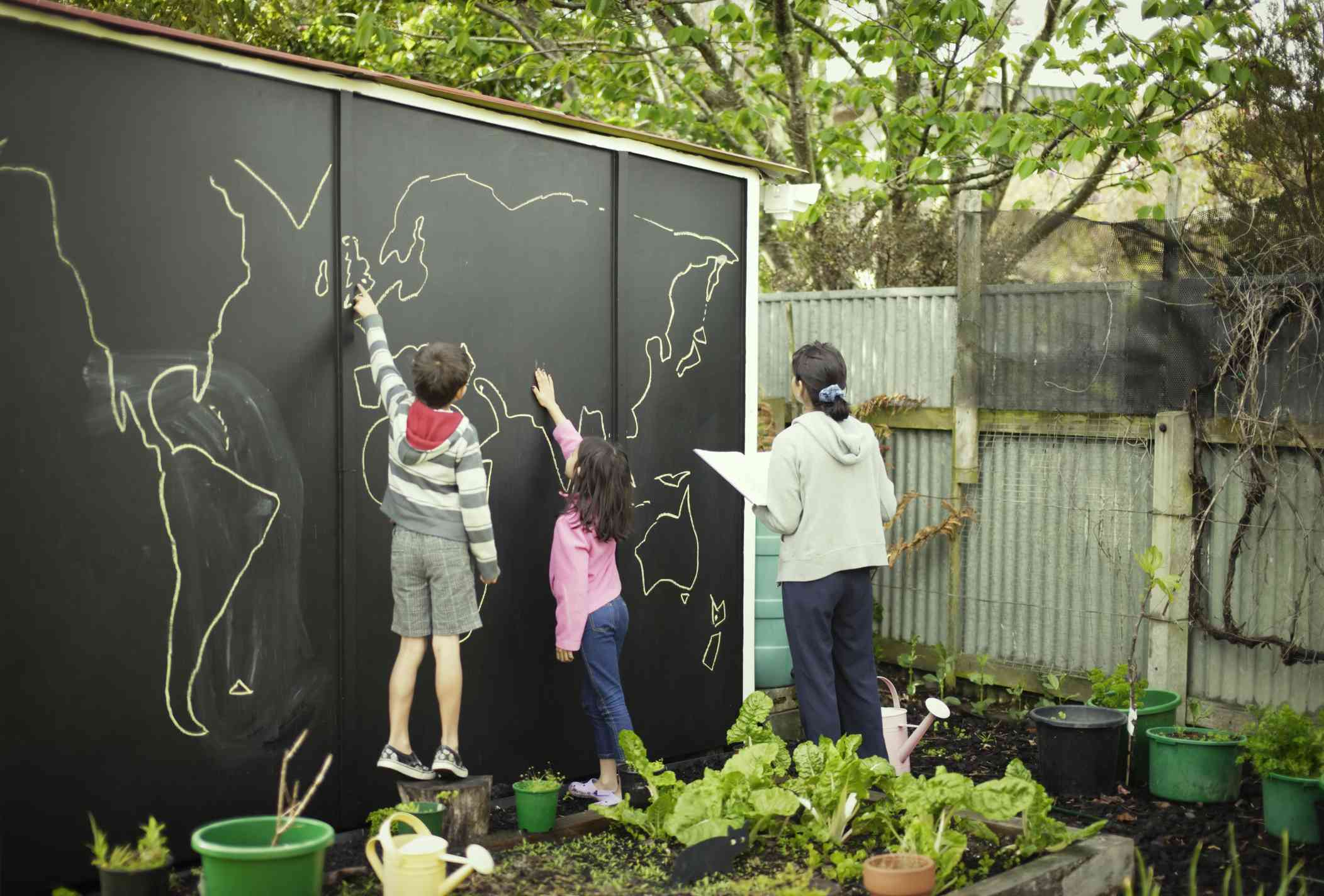 Two kids and an adult drawing a world map on a giant outdoor chalkboard.