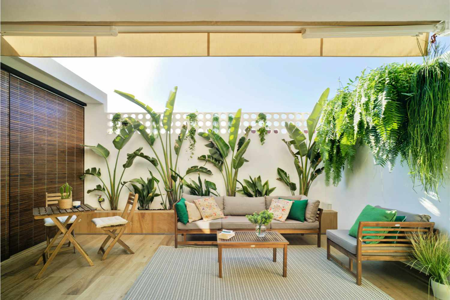 Giant foliage adorning wall in outdoor patio space.