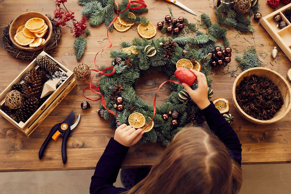 girl decorating holiday wreath