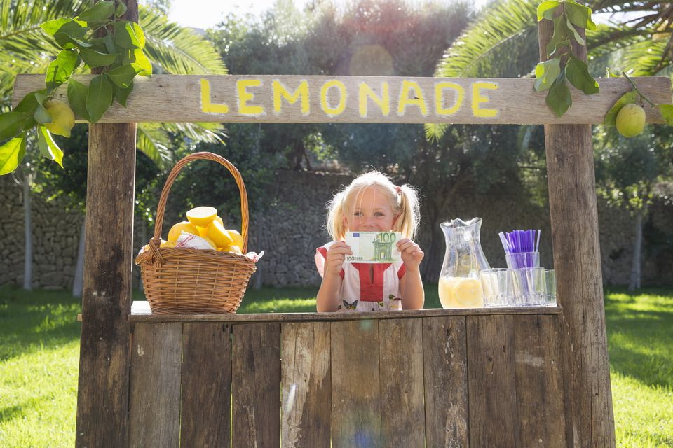 Portrait of girl on lemonade stand holding up one hundred euro note