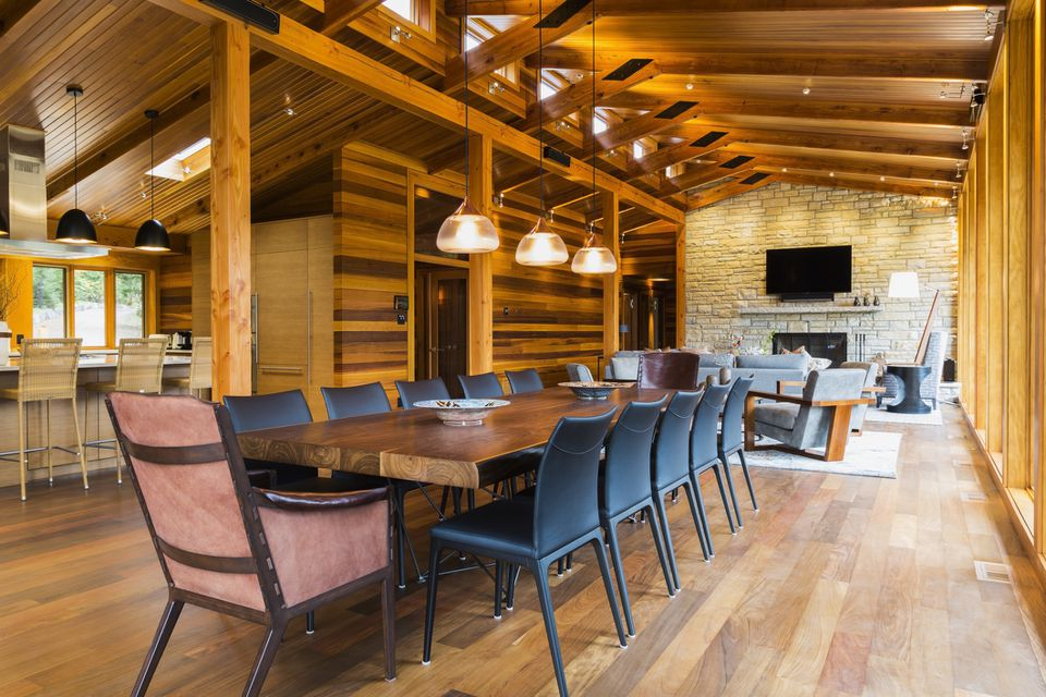 Wooden dining table with rawhide armchairs, black leather chairs and illuminated industrial style copper with frosted glass pendant lighting fixtures in dining area of great room with Ipe wood floor plus view of living room area with natural stone fireplace