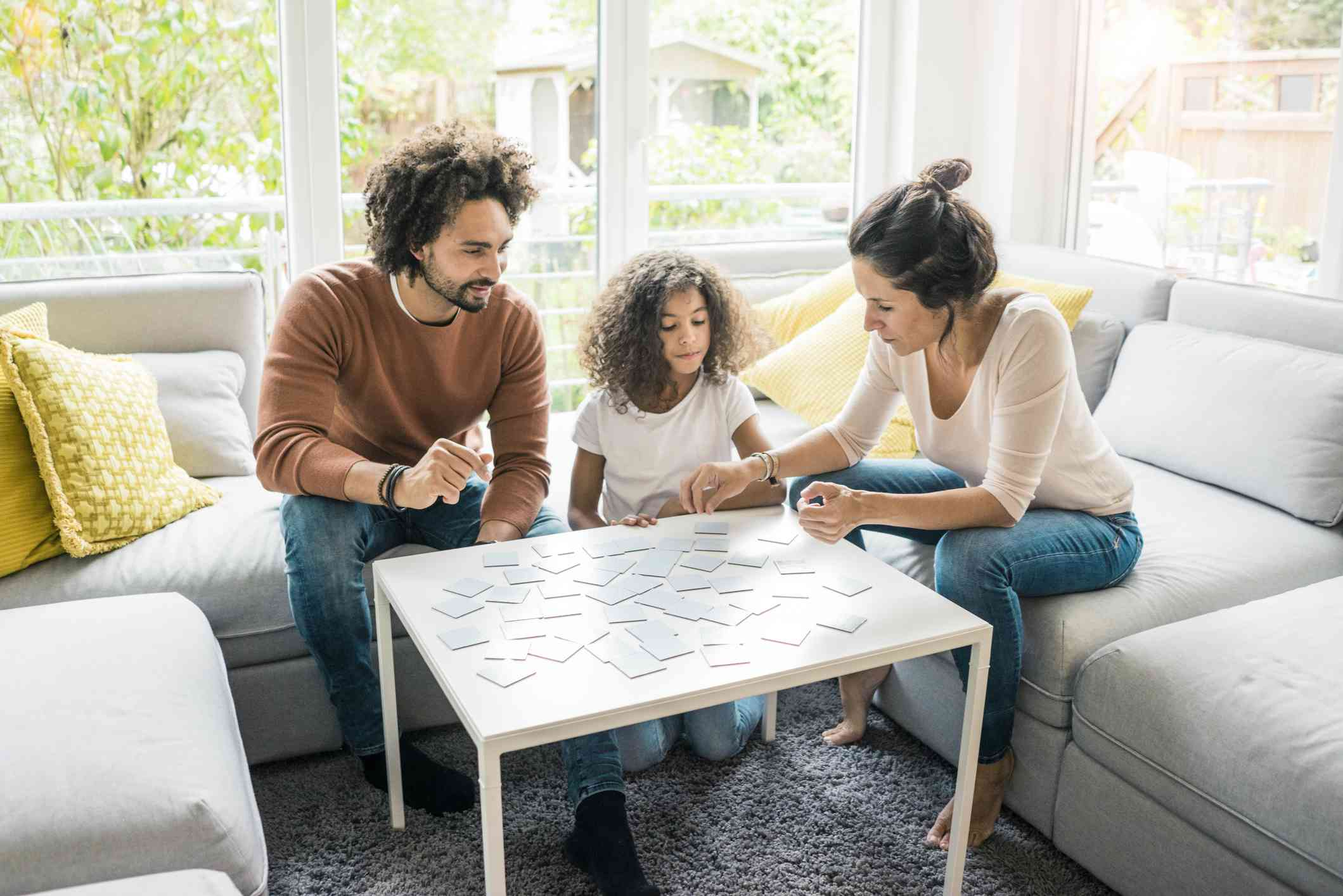 Family of three playing a board game together.
