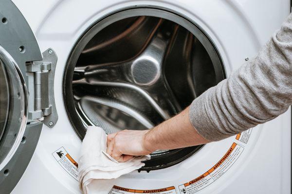 person wiping down a washing machine