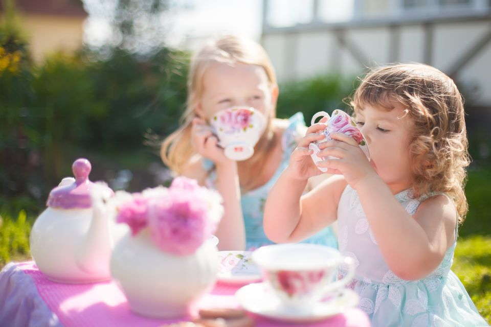 Two sisters playing tea party outdoors.