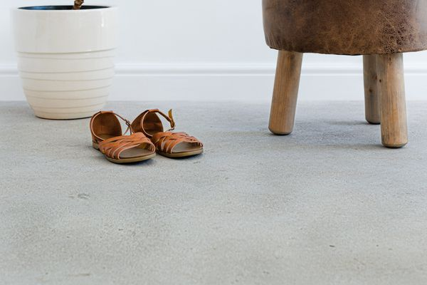 Concrete flooring with brown leather sandals in front of white plant pot and brown stand