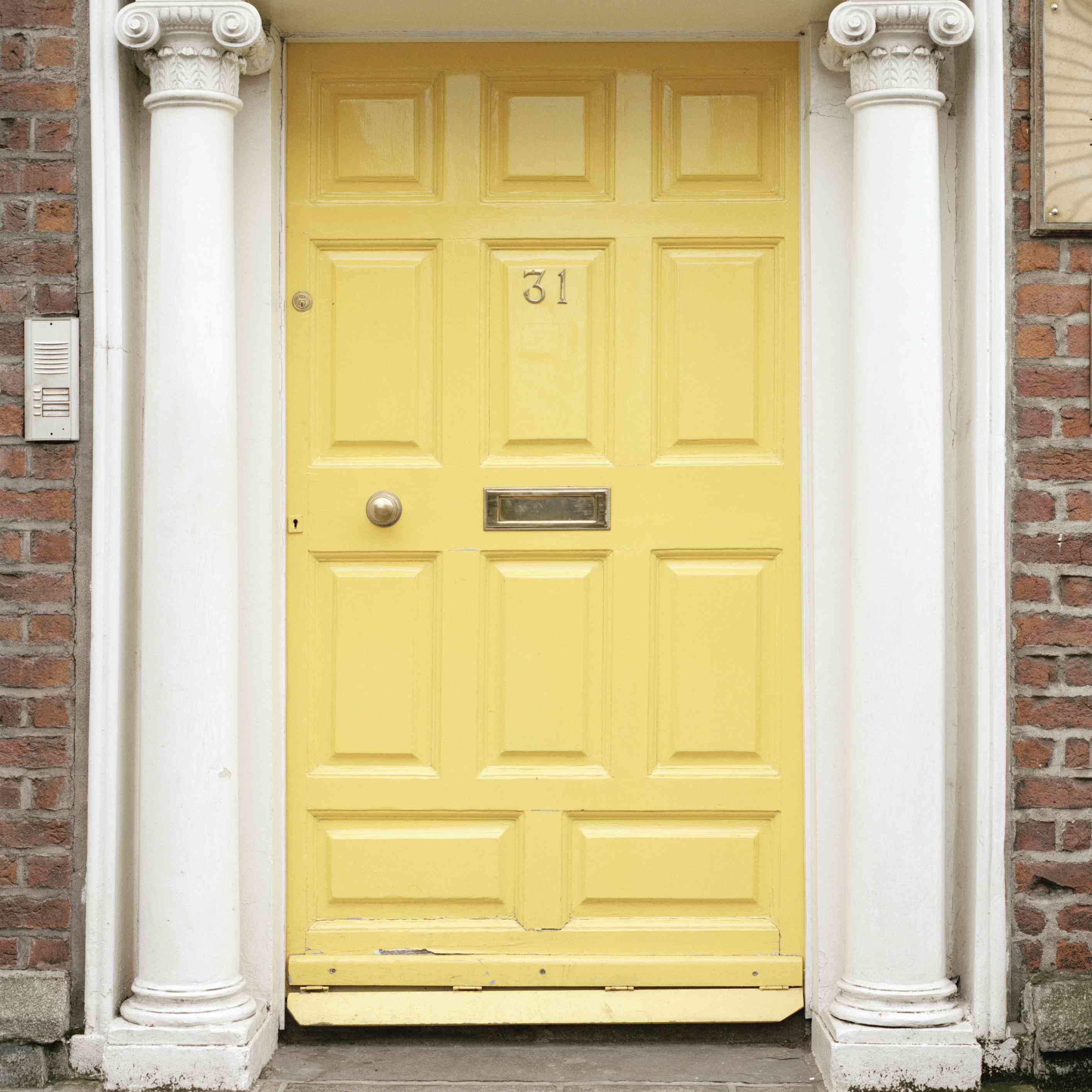 A yellow door in a home with neoclassical columns