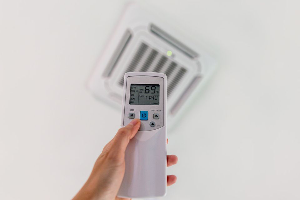 person using a remote thermostat