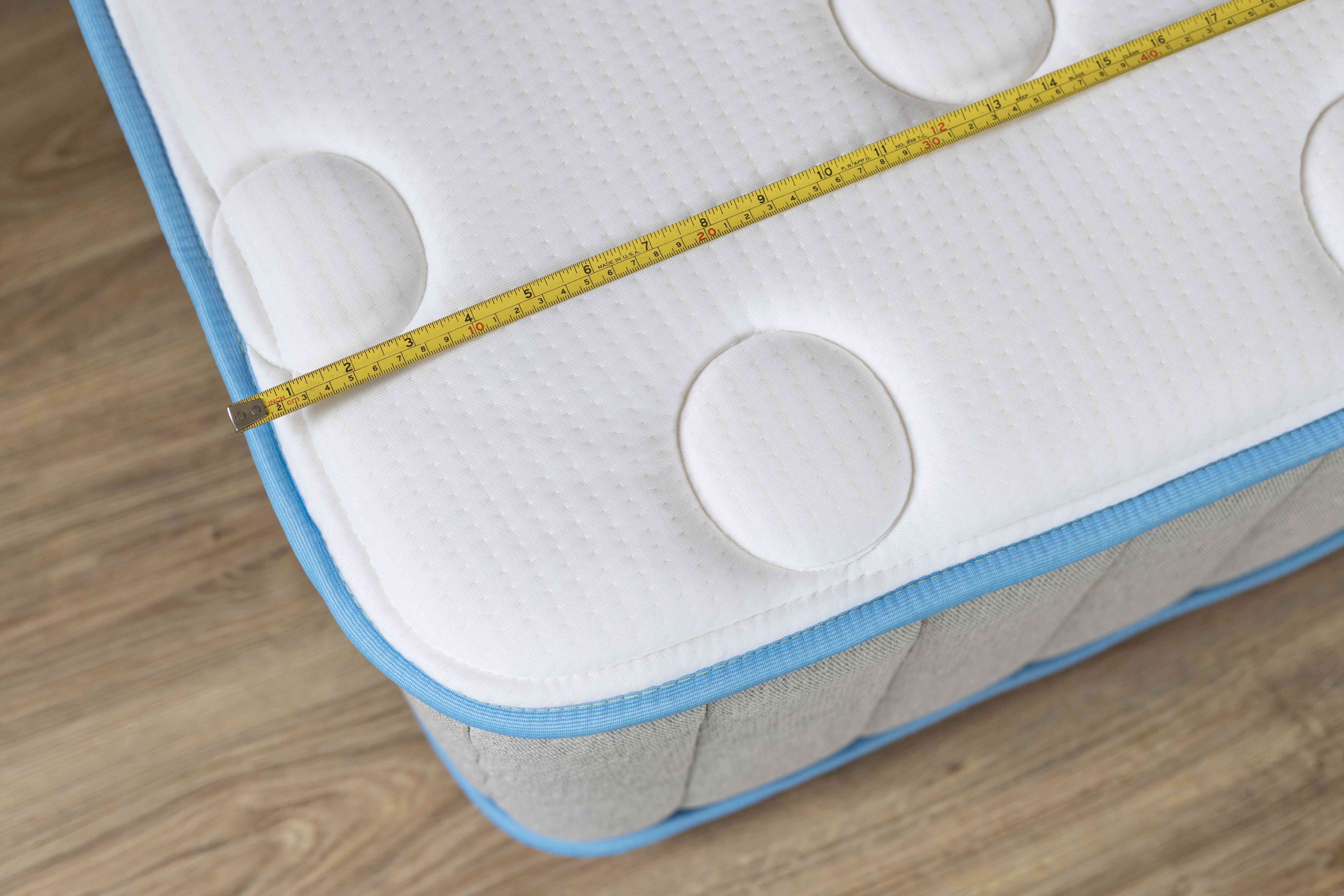 Corner of mattress with yellow measuring tape to measure for mattress bag size