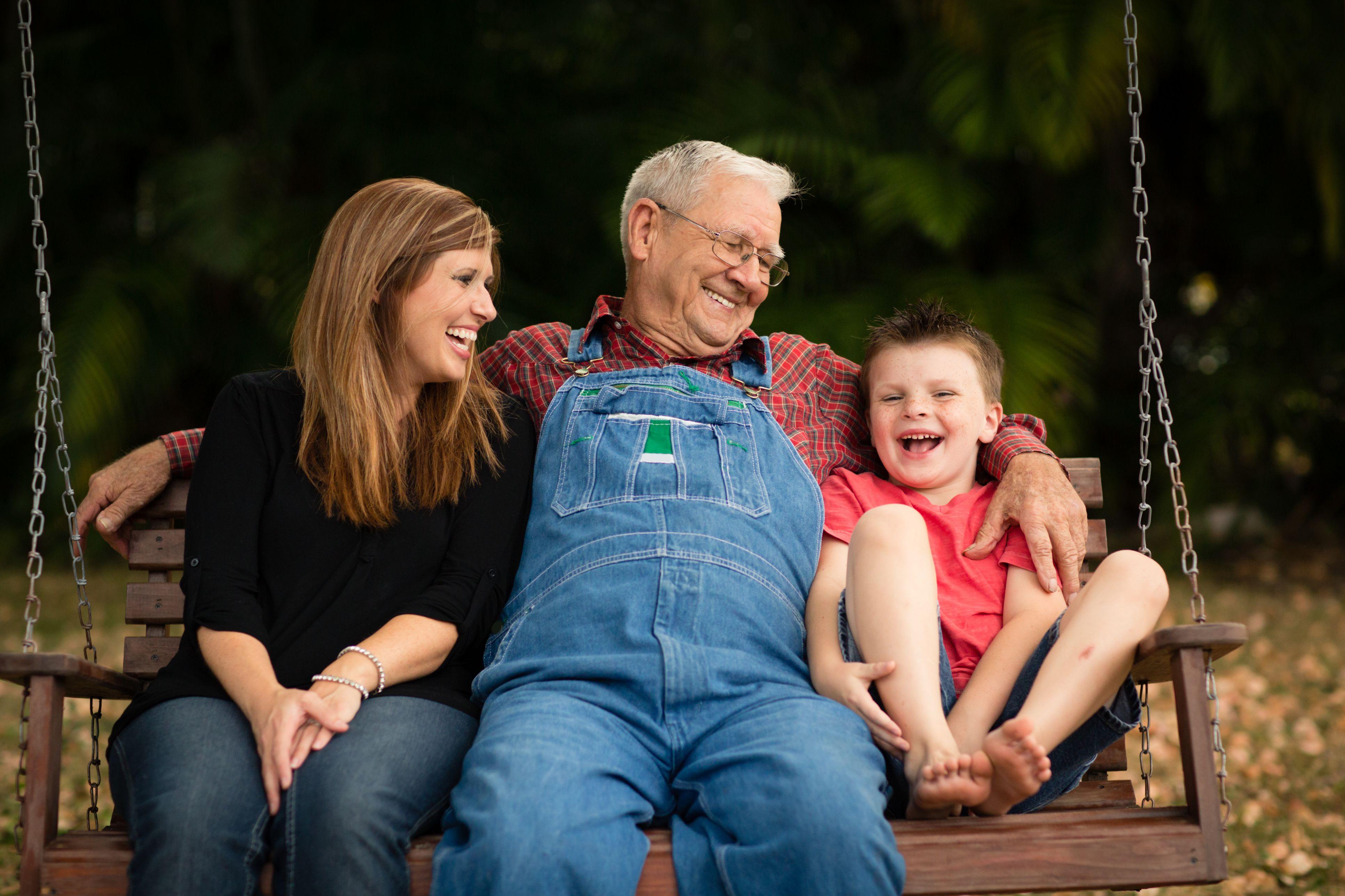 Abuelo columpiándose con su nieta y bisnieto