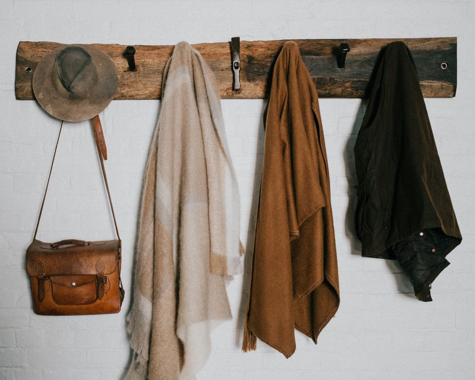 hats and scarves hanging from a coat rack