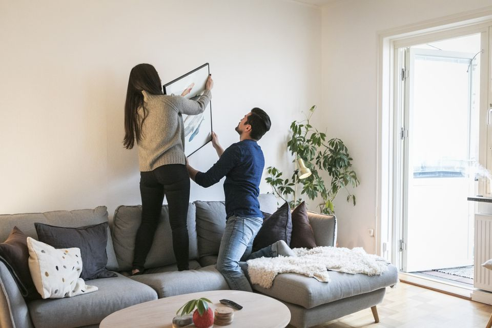 Couple adjusting photo on their home wall