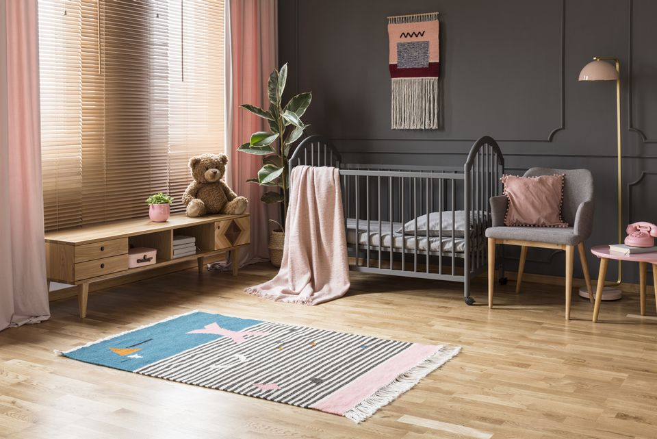Real photo of a baby crib standing between a low cupboard and an armchair, lamp and stool in child's room interior with wooden floor and grey walls with moldings
