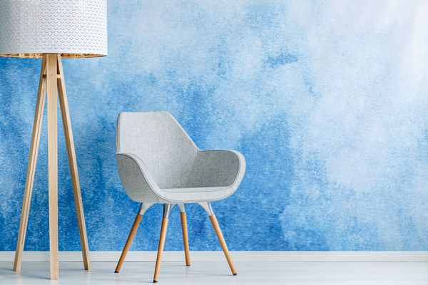 Living room interior with gray armchair and standing lamp against blue and white ombre wall with empty space. Real photo.
