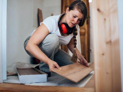 Woman installing laminate floor