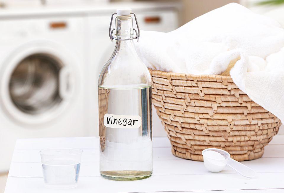 White distilled vinegar bottled next to laundry weave basket