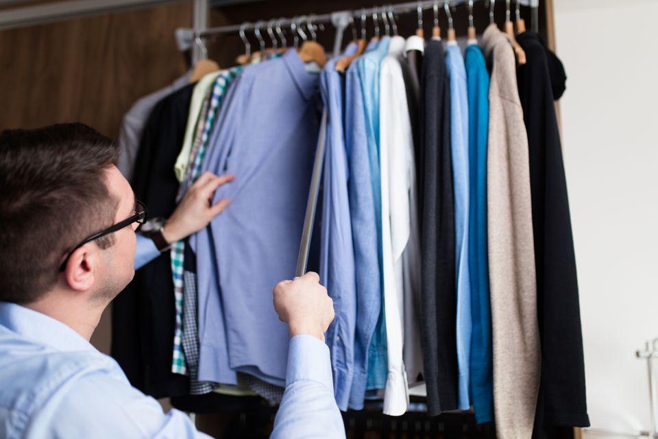 Man picking a shirt from an organized closet system