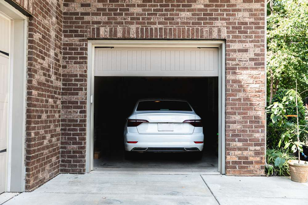 Tan garage door reversed immediately with white car inside garage