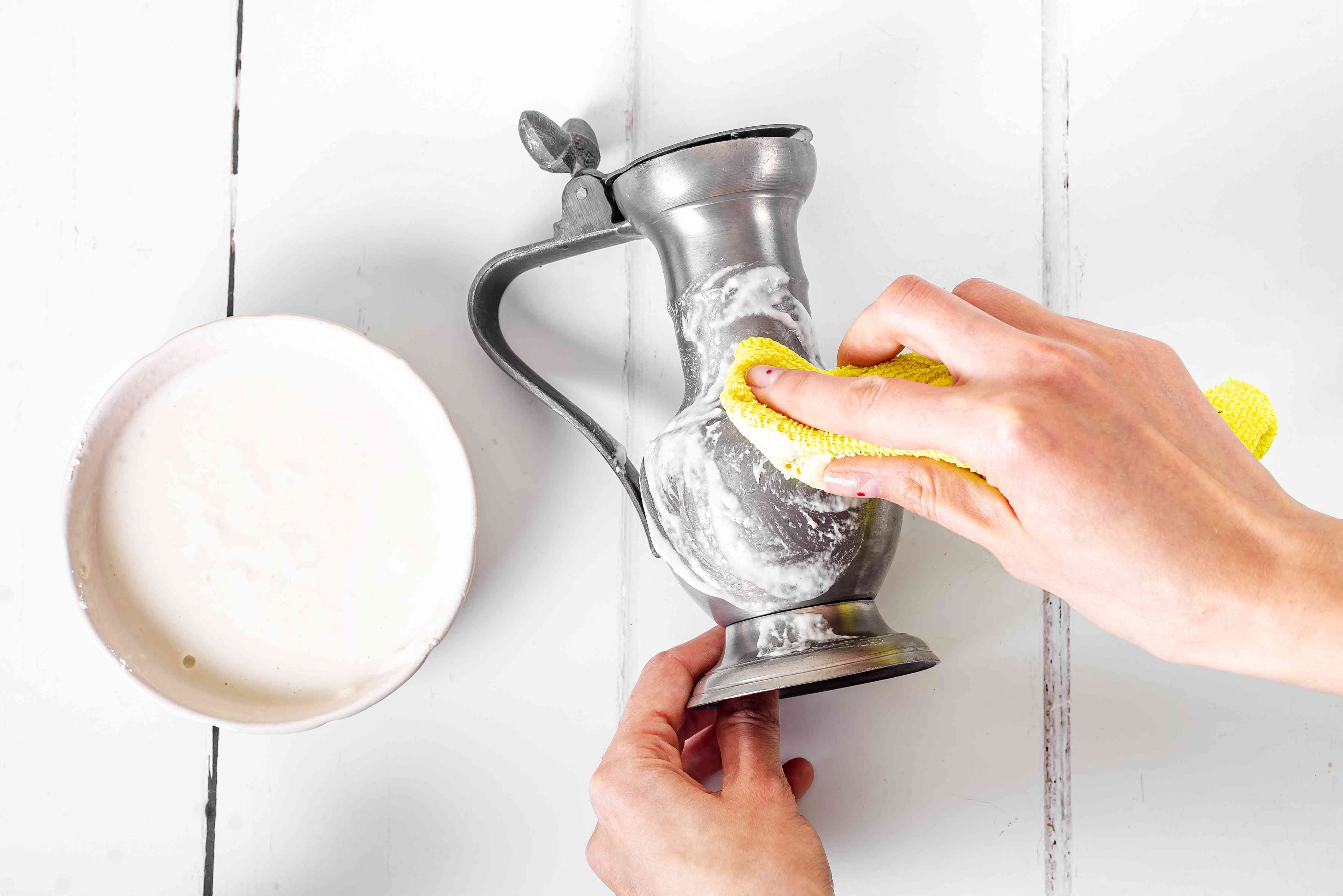 Pewter dispenser cleaned with vinegar and flour cleaning paste with yellow cloth