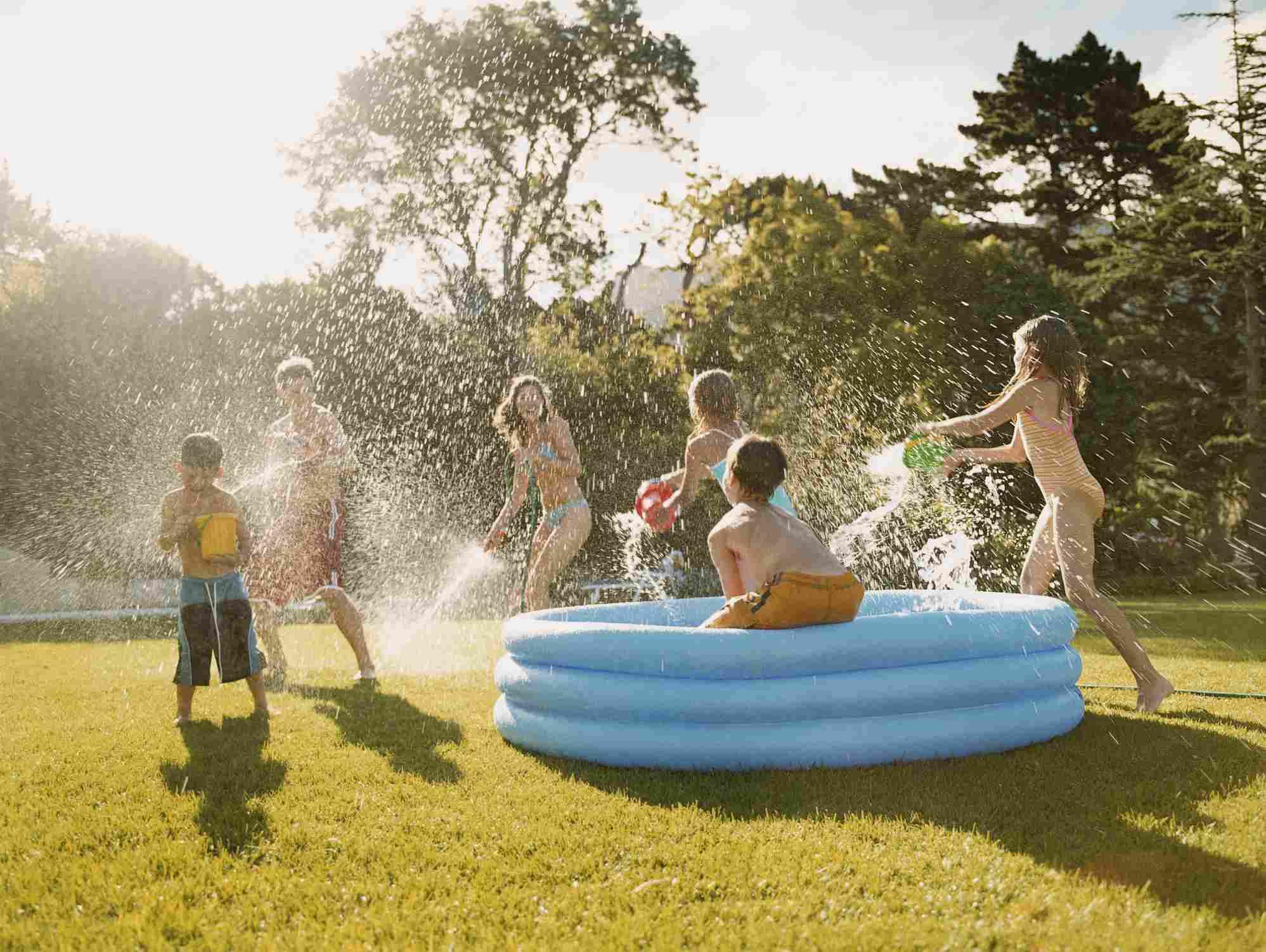 Una piscina azul para niños en el césped con niños peleando por el agua