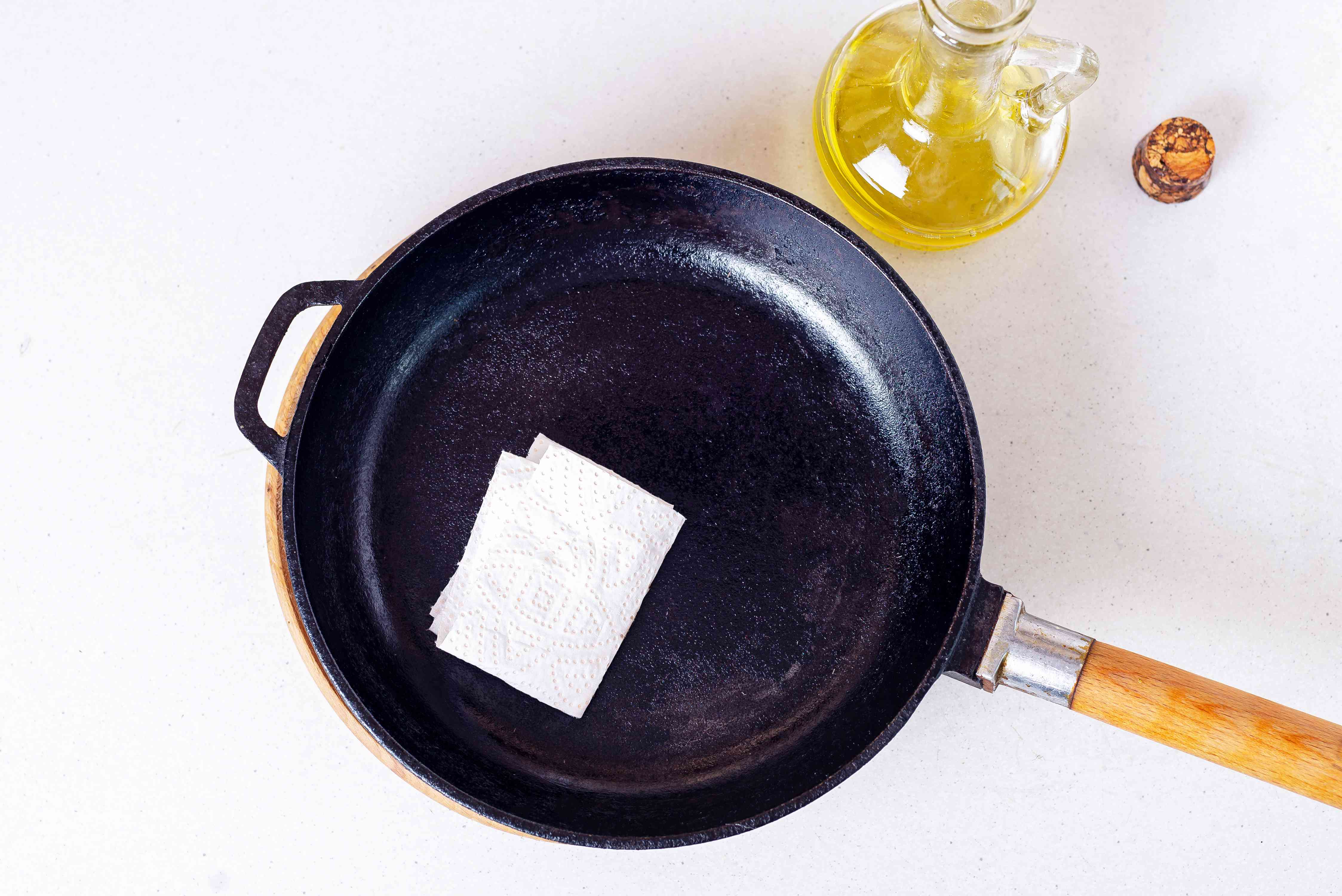 Cast iron pan re-seasoned with vegetable oil and white paper towel