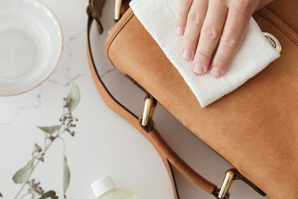 Someone cleaning a leather purse
