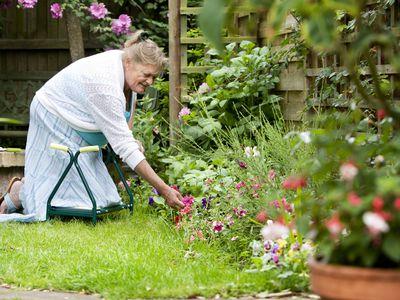 Senior woman kneeling on a kneeler in her garden outdoors.