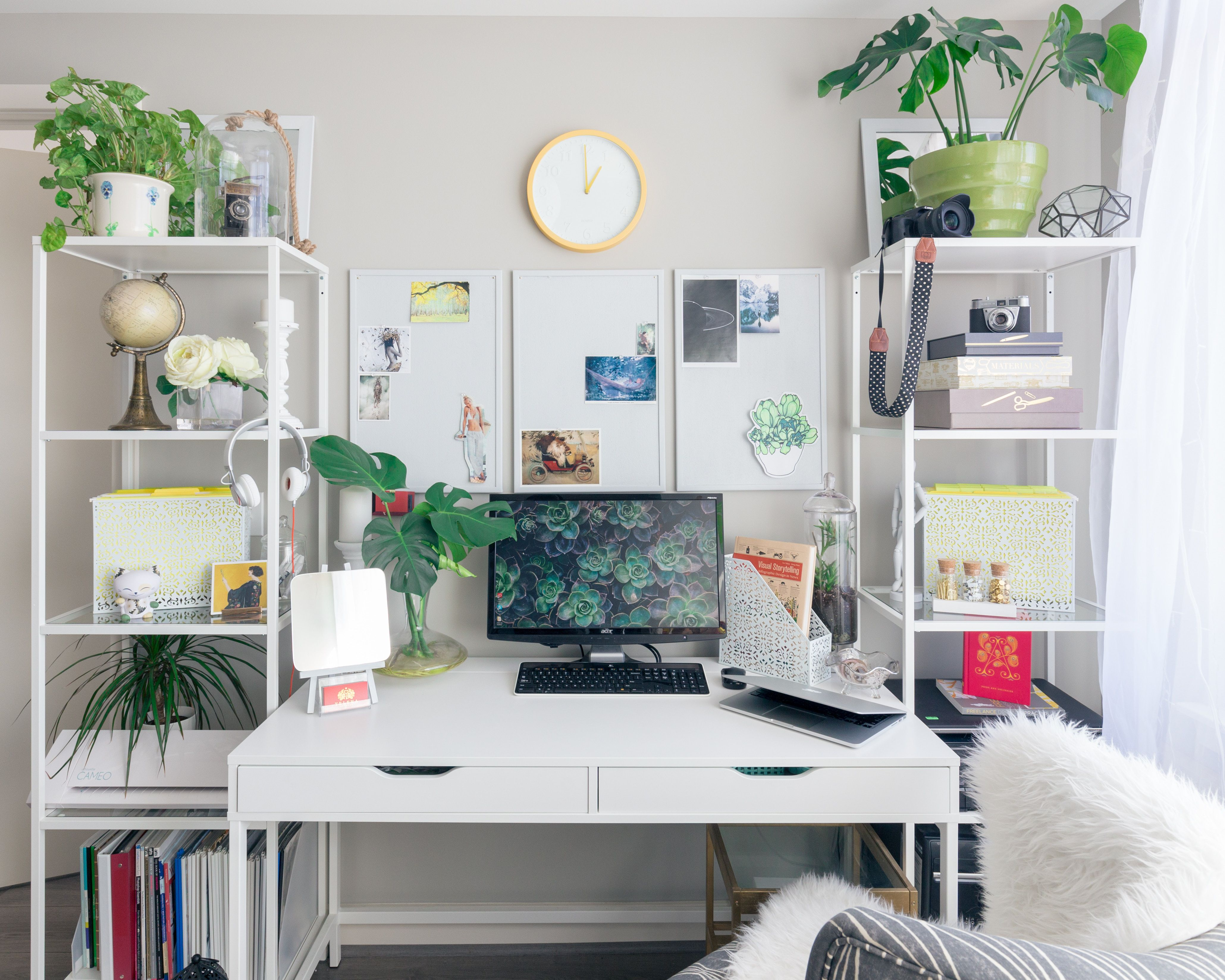 Desk with accessories and objects scattered around it and next to it on shelves