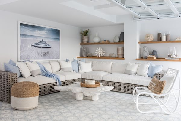 A ground-floor entertaining area opens to a lanai and pool via a glass garage door at the Long Beach Island home of Karen B. Wolfe