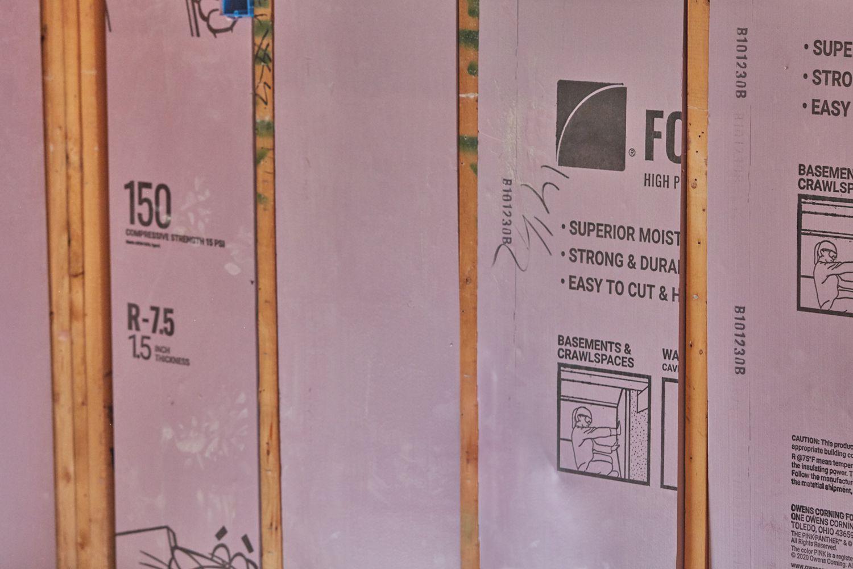 Pink foam insulation in between wooden structure beams