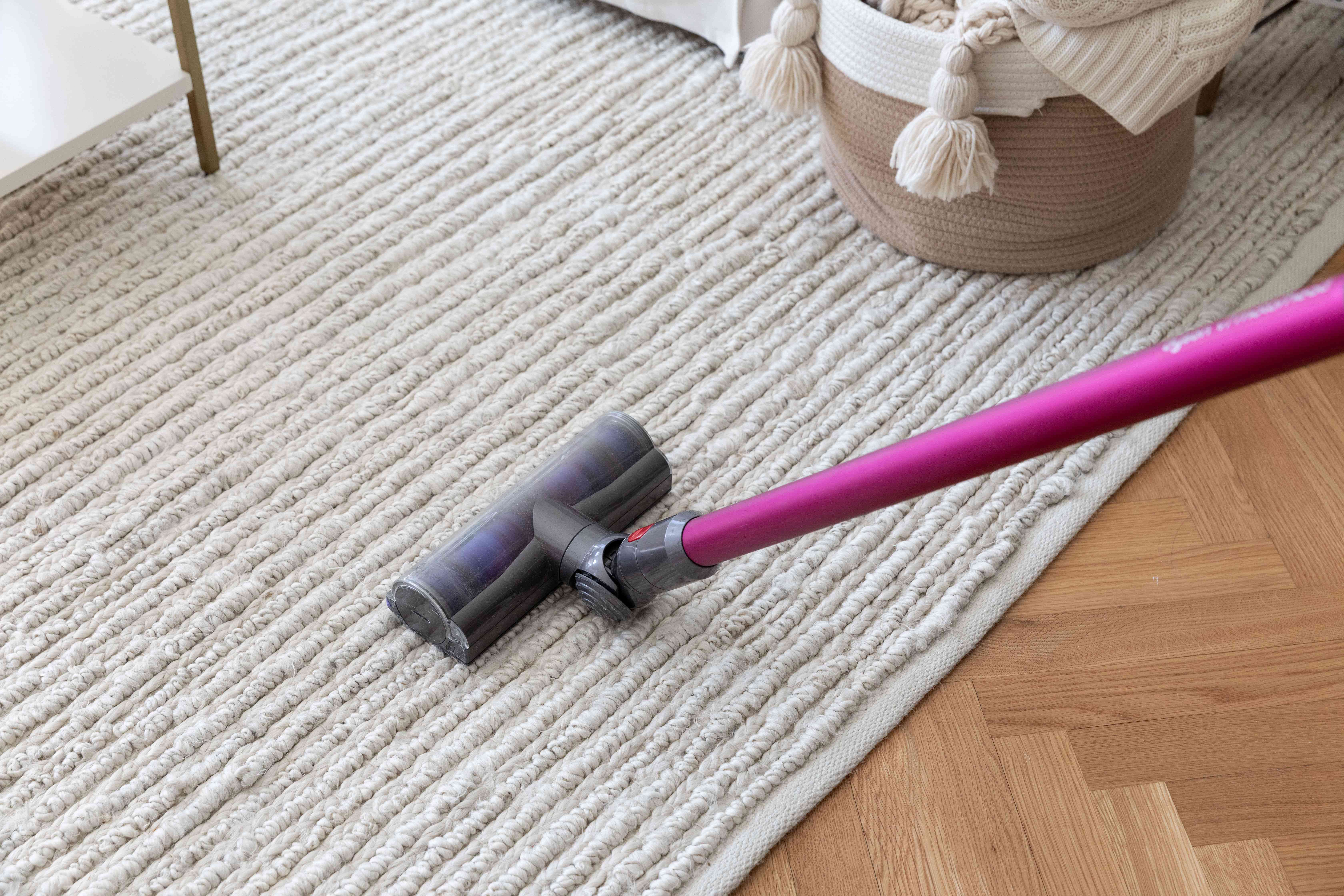 Pink handled vacuum passing over beige rug for cleaning
