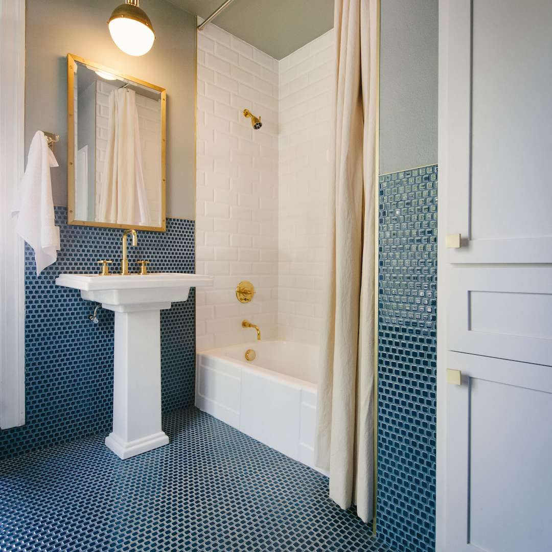 Gold fixtures in blue and green bathroom