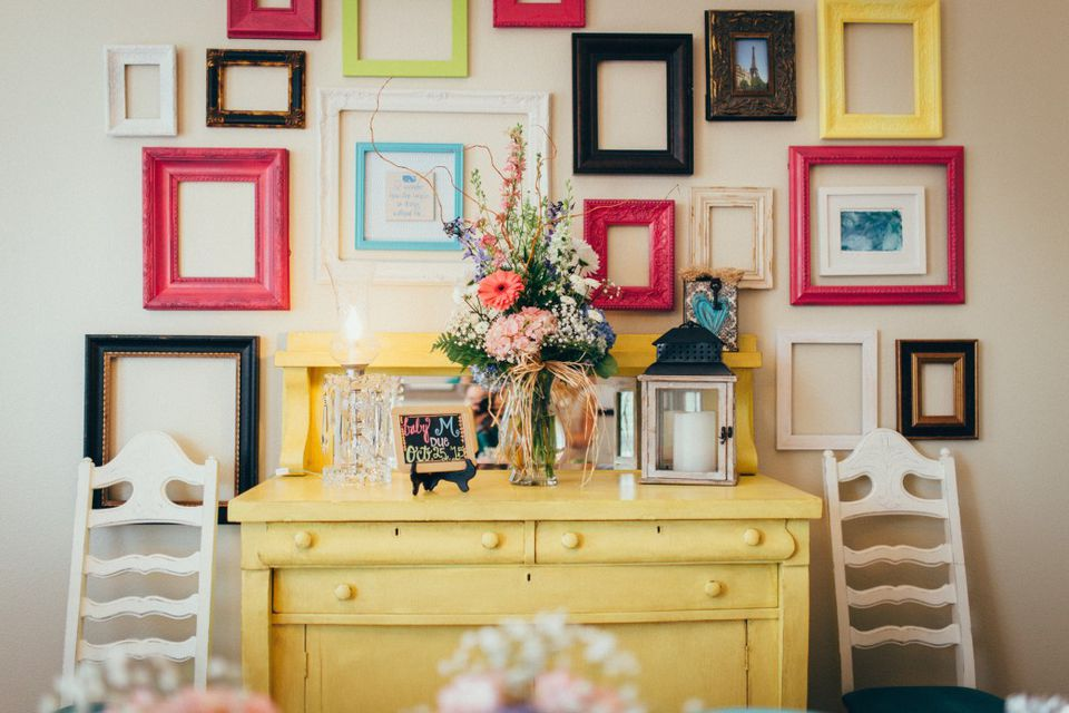 Yellow cabinet with a wall of picture frames