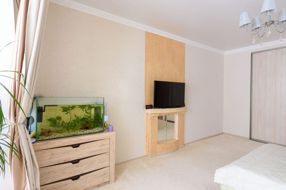 A fragment of the bedroom interior, a view of the wall opposite the bed, there is an aquarium against the wall and a TV hanging